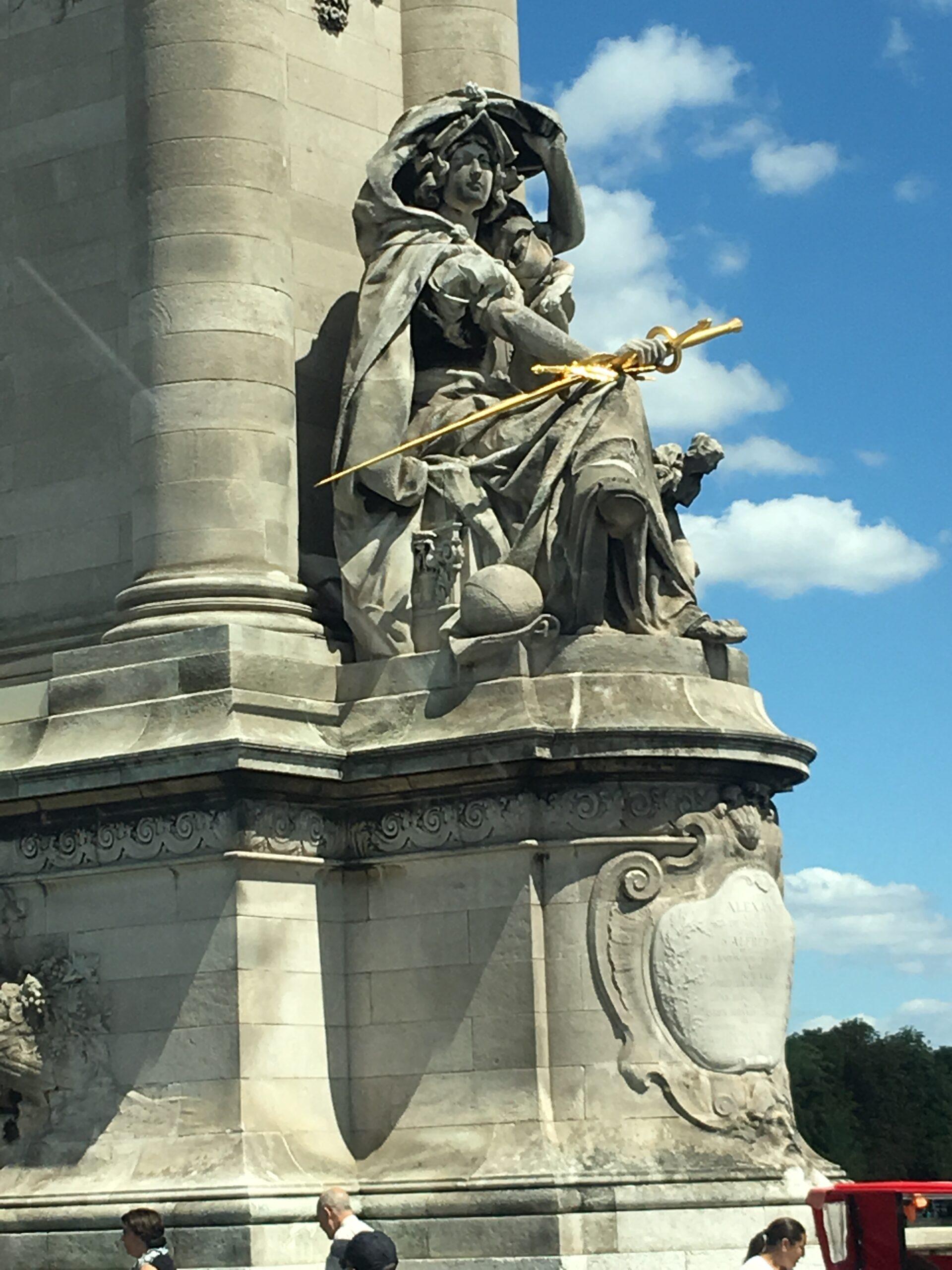 Statue of woman holding golden sword at Pont Alexandre III in Paris